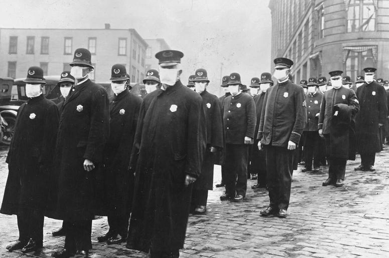 Полицейские стоят на улице в Сиэтле, штат Вашингтон, в защитных масках, изготовленных Обществом красного креста Сиэтла, во время эпидемии гриппа в 1918 г.