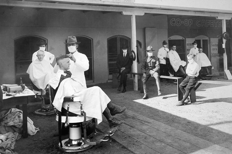 Цирюльня на улице. Было рекомендовано проводить все публичные события на открытом воздухе, чтобы сдержать распространение болезни. Фотография сделана в Калифорнийском университете, Беркли, в 1919 г.