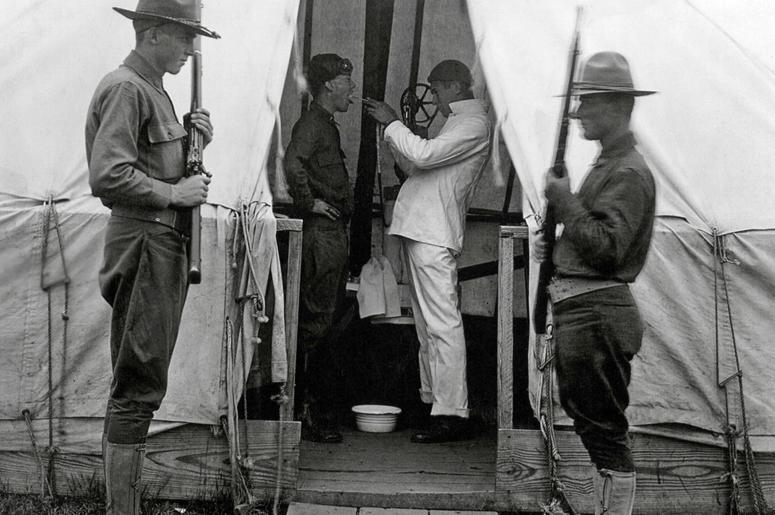 Американскому солдату обрабатывают горло спреем с целью защиты от гриппа в Лав Филд в Далласе, Техас, декабрь 1918 г.