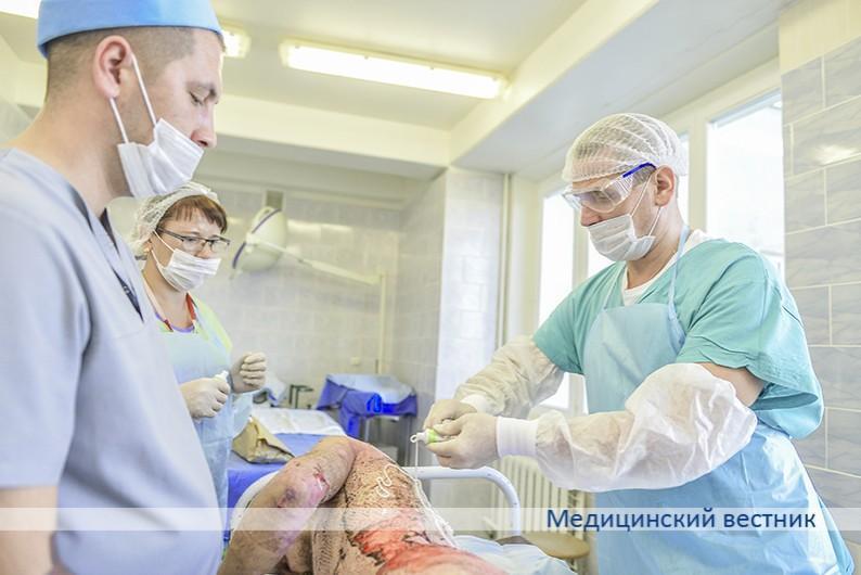 Молодой человек получил значительные ожоги, пострадало 45 % поверхности тела. Оперирован по поводу последствий обширных ожогов. Перевязочная медсестра и врач- комбустиолог Алексей Бондаренко (справа) проводят обработку антисептиком.