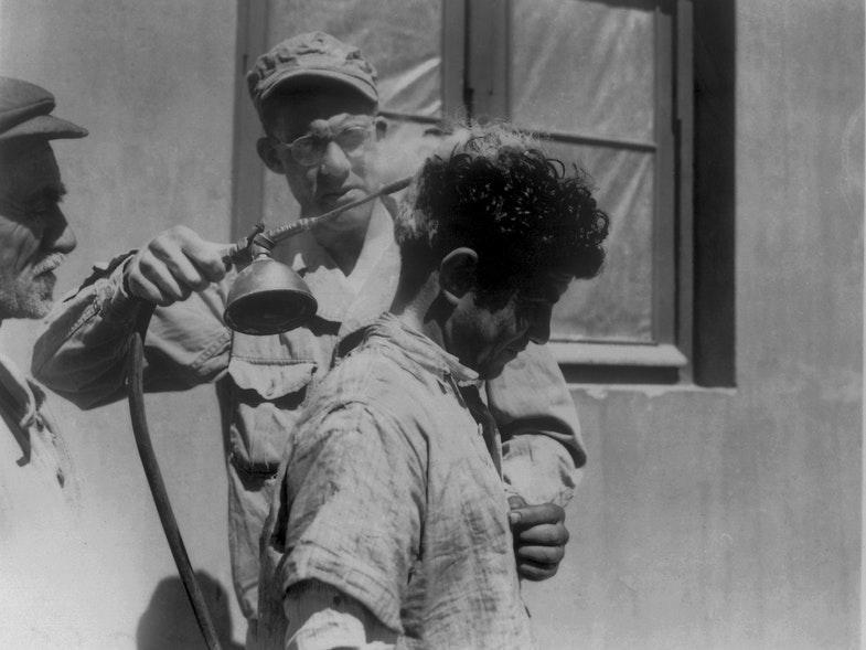 Солдат США распыляет ДДТ над головой человека.