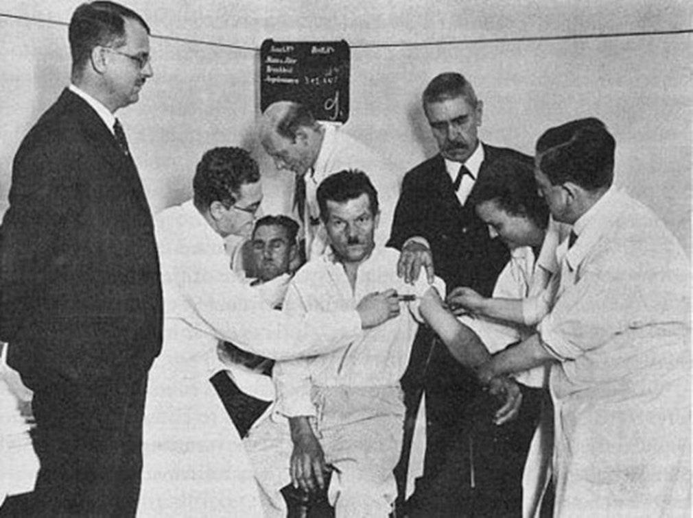 Вагнер-Яурегг (справа в центре в черном пиджаке) наблюдает за переливанием крови больного малярией больному нейросифилисом (в центре), 1934 год. Фото: wikimedia.org