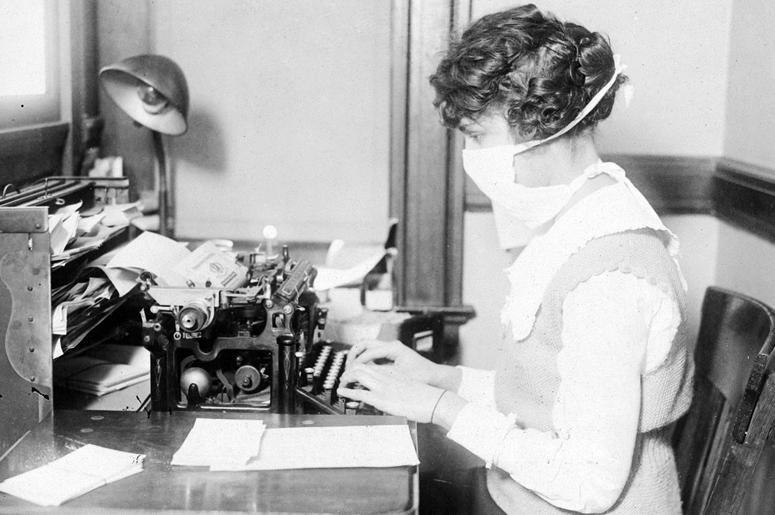 Машинистка в маске для защиты от гриппа. Обеспокоенные информацией о том, болезнь достигла Нью-Йорка, практически все рабочие закрыли свои лица марлевыми повязками, чтобы защититься от болезни. Октябрь 1918 г.